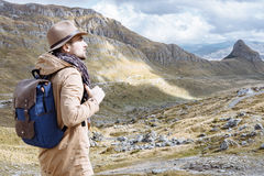 Man traveler with hat and backpack looking on top of the hill, D Stock Photos