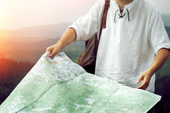 Man traveler holding exploring map close-up on top of sunny hill Royalty Free Stock Photo