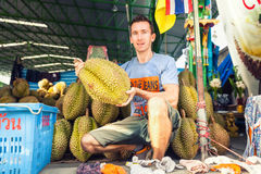 Man traveler holds in hand tropical fruit Durian Stock Photo
