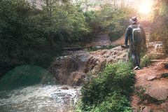 A man, a traveler in a leather jacket and a cowboy hat and backpack. Large full-flowing waterfall with dirty water, a journey, stock images