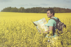 Man traveler with map in hand looking at it against the background of sunlit meadows. Royalty Free Stock Photos