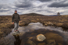 Man traveler on marshland Stock Photos