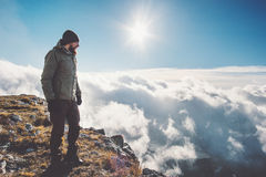 Man Traveler on mountain cliff over clouds Royalty Free Stock Image