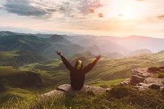 Man Traveler on mountain summit enjoying aerial view hands raised Travel Lifestyle success concept adventure active vacations. Outdoor happiness freedom stock photography
