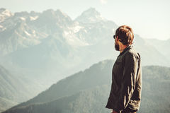 Man Traveler at mountains hiking Travel Lifestyle. Concept adventure vacations outdoor mountains landscape on background Stock Images