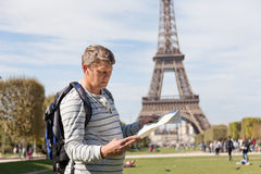 Man - the traveler near the Eiffel Tower. Looks in a map of the city Royalty Free Stock Photography