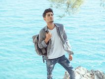 Man traveler near the sea. Traveler with backpack on the rocks near the sea looking away. Summer Travel Vacation. Handsome young caucasian tourist man in casual Stock Photography