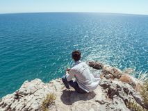 Man traveler near the sea. Traveler on the rocks near the sea looking far away at horizon. Summer Travel Vacation. Handsome young caucasian tourist man in casual Royalty Free Stock Photography