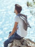 Man traveler near the sea. Traveler on the rocks near the sea looking far away at horizon. Summer Travel Vacation. Handsome young caucasian tourist man in casual Stock Photos