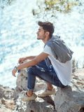 Man traveler near the sea. Traveler on the rocks near the sea under a tree looking away. Summer Travel Vacation. Side view of handsome young caucasian tourist Stock Photo
