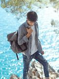 Man traveler near the sea. Traveler with backpack on the rocks near the sea looking down. Summer Travel Vacation. Handsome young caucasian tourist man in casual Stock Photo