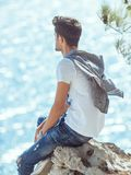 Man traveler near the sea. Traveler on the rocks near the sea looking at camera. Summer Travel Vacation. Handsome young caucasian tourist man in casual clothes Royalty Free Stock Photo