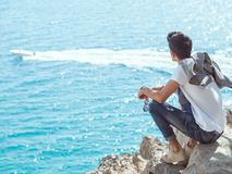Man traveler near the sea. Traveler on the rocks near the sea looking far away at boat. Summer Travel Vacation. Handsome young caucasian tourist man with Royalty Free Stock Photo