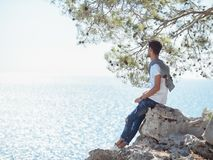 Man traveler near the sea. Traveler on the rocks near the sea looking far away at horizon. Summer Travel Vacation. Handsome young caucasian tourist man with Stock Images