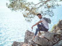 Man traveler near the sea. Traveler on the rocks near the sea under a tree looking at camera. Summer Travel Vacation. Side view of handsome young caucasian Stock Photos