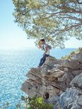 Man traveler near the sea. Traveler standing near steep on the rocks near the sea under a tree and looking away. Summer Travel Vacation. e view of handsome young Royalty Free Stock Image