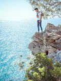 Man traveler near the sea. Traveler standing near steep on the rocks near the sea under a tree and looking down. Summer Travel Vacation. e view of handsome young Stock Images