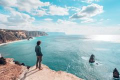 Man traveler over cold sea landscape. Back view of man traveler standing on mountain alone and looking at autumn sea landscape. Hiking in cold season. Wanderlust Royalty Free Stock Photography