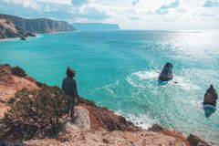 Man traveler over cold sea landscape. Back view of man traveler standing on mountain alone and looking at autumn sea landscape. Hiking in cold season. Wanderlust Stock Image