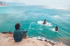 Man traveler over cold sea landscape. Man traveler sitting on mountain alone and looking at autumn sea landscape. Hiking in cold season. Wanderlust concept scene Royalty Free Stock Images
