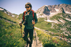 Man Traveler with photo camera and backpack hiking Stock Photo