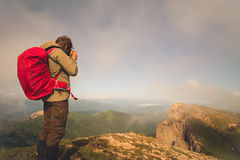Man Traveler with photo camera and backpack hiking outdoor Royalty Free Stock Image