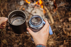 Man traveler pours water from a bottle into a metal mug. Bushcraft, adventure, travel, tourism and camping concept royalty free stock images