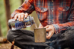 Man traveler pours water from a bottle into a metal mug. Royalty Free Stock Photography