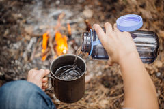 Man traveler pours water from a bottle into a metal mug. Bushcraft, adventure, travel, tourism and camping concept stock photos
