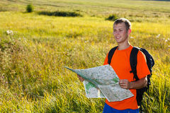 Man traveler with read the map and smiles. Against a background of green nature Royalty Free Stock Image
