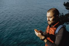 Man traveler in a red waistcoat watching world map on mobile pho. Ne while relaxing near sea Stock Photos