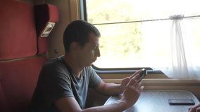 Man traveler relaxing on train listening to music and smiling through the pictures via social media. Slow motion video
