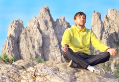 Man Traveler Relaxing Yoga Meditation sitting on stones with Rocky Mountains. Peak Ai-Petri and blue sky on Background Royalty Free Stock Photography
