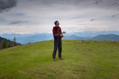Man traveler, with remote controller of drone, stands on the alp Royalty Free Stock Photo