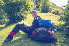 Man traveler sits on an alpine meadow with map Stock Images