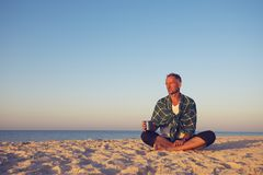 Man traveler sits on the deserted seashore. Drinks coffee and meditated during sunset Royalty Free Stock Photos