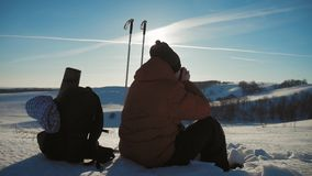 Man traveler sits resting on a cliff in the winter mountains and drinks tea from a thermos. Rear view of young man stock video footage
