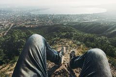 Man traveler sits on top and enjoys view of the picturesque landscape and the city. Point of view shot. Travel, adventure, tourism. Male traveler sits on top and royalty free stock photography