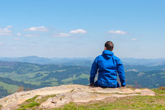Man, traveler sitting on the edge of a cliff and Stock Photos