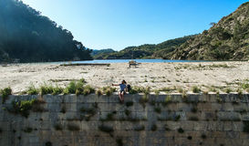 Man traveler sitting on a edge of the dam and taking selfie photo stock photos