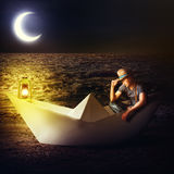 Man traveler sitting in fantasy paper boat Royalty Free Stock Photo