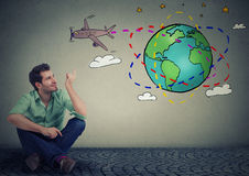 Man traveler sitting on floor thinking about an amazing trip around the world Royalty Free Stock Photos