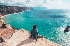 Man traveler over cold sea landscape. Man traveler sitting on mountain alone and looking at autumn sea landscape. Hiking in cold season. Wanderlust concept scene Royalty Free Stock Photo