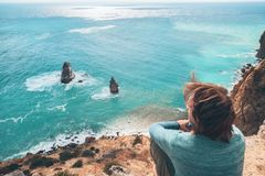 Man traveler over cold sea landscape. Man traveler sitting on mountain alone and looking at autumn sea landscape. Hiking in cold season. Wanderlust concept scene Royalty Free Stock Image
