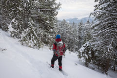 Man traveler in snowshoes relax among snow covered fir trees Stock Photo