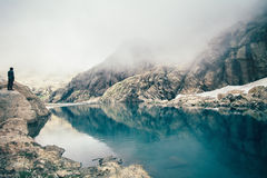 Man Traveler standing alone on cliff lake Royalty Free Stock Photo