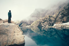 Man Traveler standing alone on stone cliff lake and misty mountains on background Royalty Free Stock Photos