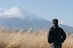 Man traveler standing and looking Beautiful Mount Fuji with snow capped and blue sky at Lake kawaguchiko, Japan royalty free stock photo