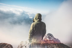Man Traveler standing on mountain summit. With clouds around Travel Lifestyle success concept adventure active vacations outdoor rear view Royalty Free Stock Photo