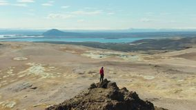 Man Traveler Stands on Mountain Top. Iceland. Aerial View. Man Traveler Stands on Mountain Top in Hverir Area. Icelandic Landscape. Iceland. Aerial View. Drone stock video footage